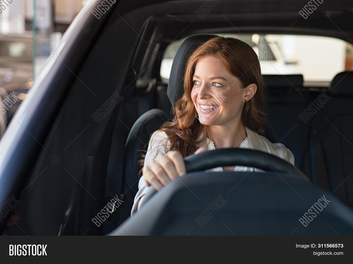 Mature beautiful woman sitting in car looking away while trying new automobile. Portrait of daydream