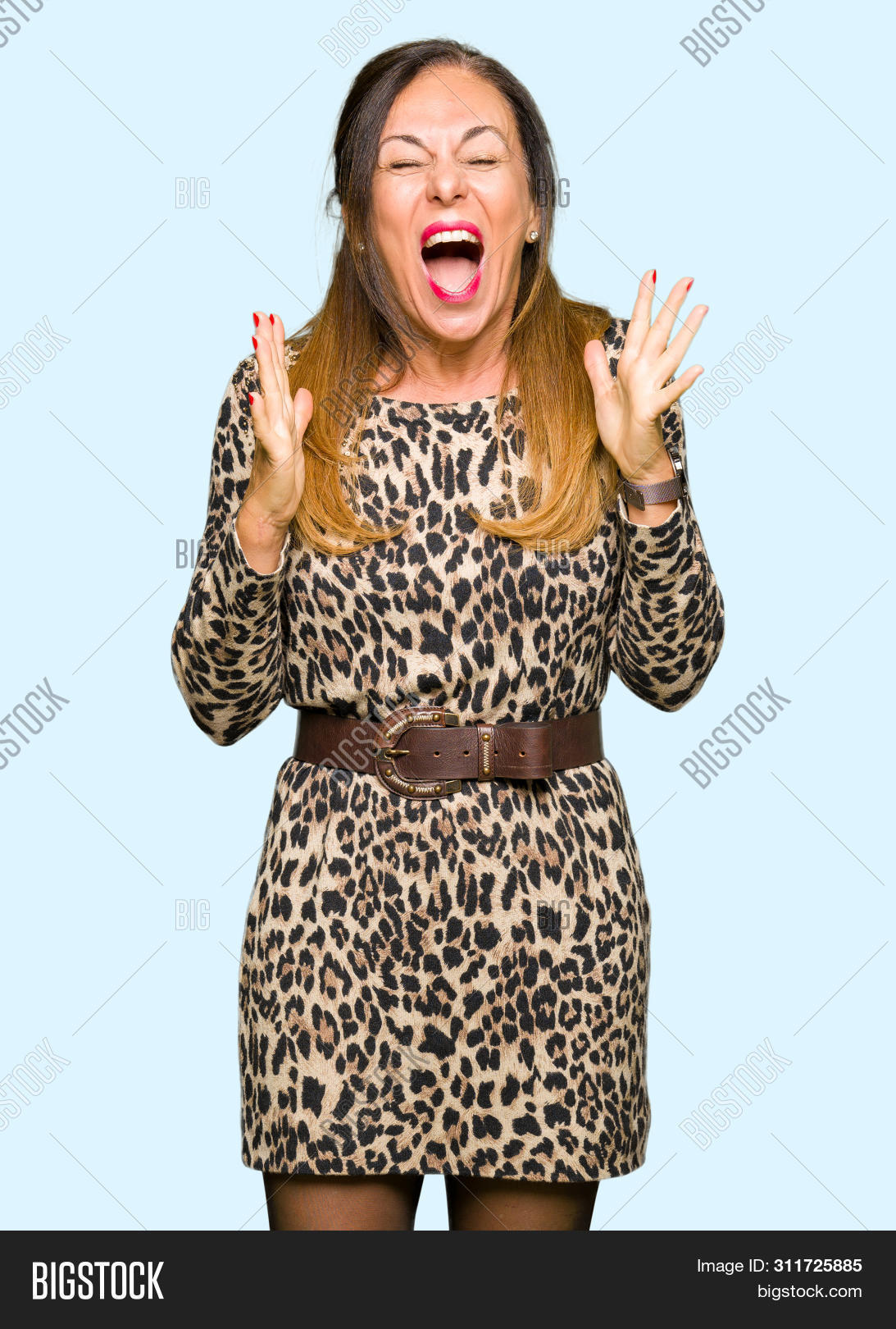 Beautiful middle age woman wearing leopard animal print dress celebrating mad and crazy for success with arms raised and closed eyes screaming excited. Winner concept