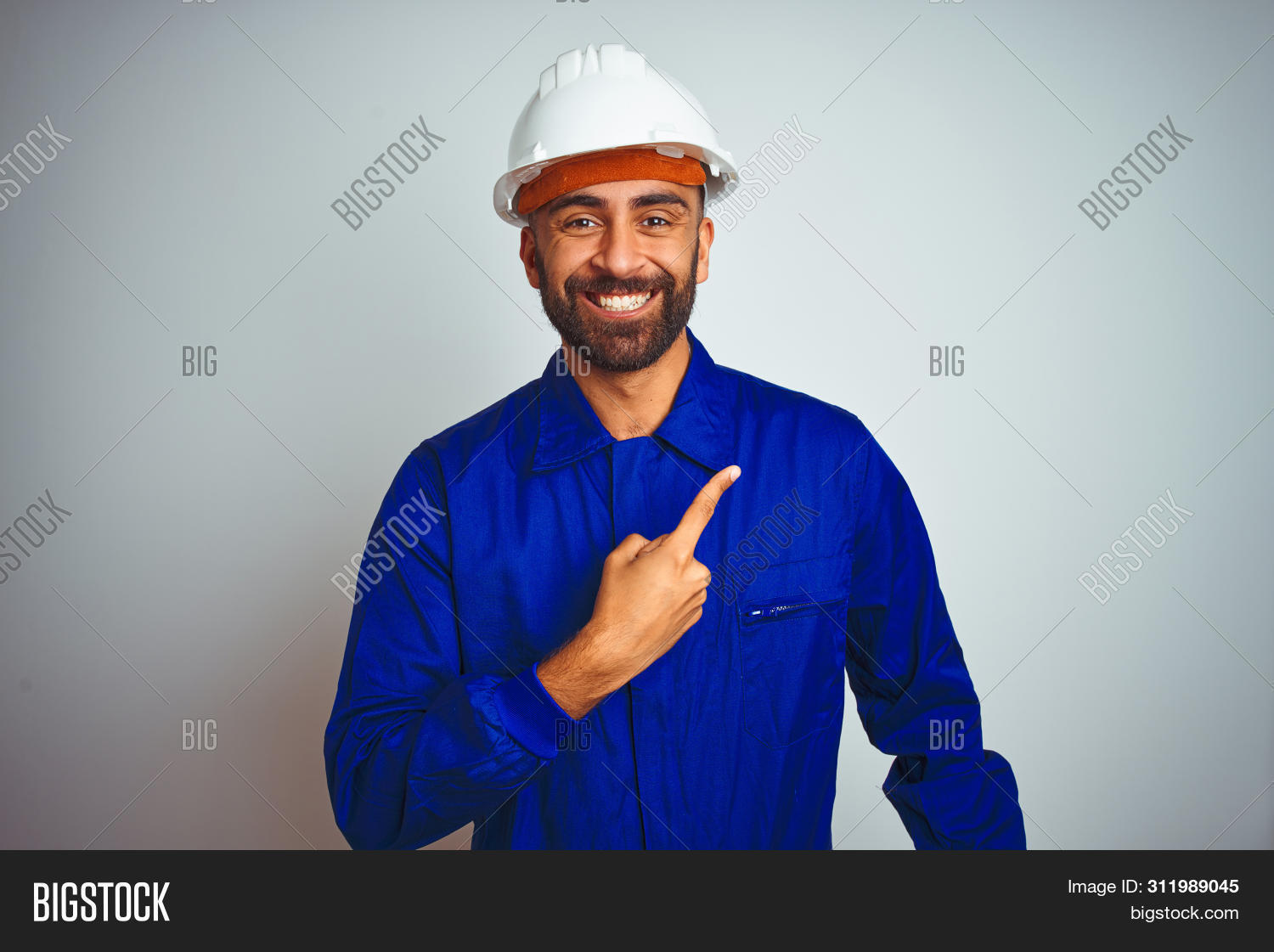 adult,advertisement,arab,background,builder,camera,cheerful,confident,construction,contractor,emotion,engineer,expression,face,finger,fingers,gesture,hand,happy,hardhat,helmet,hispanic,indian,industry,isolated,looking,man,natural,one,person,point,pointing,portrait,presenting,product,safety,showing,side,sign,smile,smiling,space,trust,uniform,up,view,welcome,white,worker,young