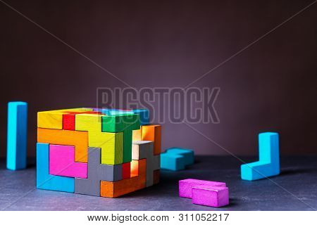 Cube of multi-colored wooden shapes. Concept of decision making process, creative, logical thinking. Choose correct answer. Logical tasks. Conundrum, find the missing piece of the proposed. stock photo