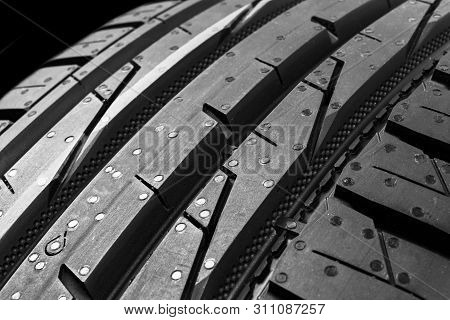 Studio shot of a set of summer car tires isolated on black background. Tire stack background. Car tyre protector close up. Black rubber tire. Brand new car tires. Close up black tyre profile. Car tires in a row stock photo