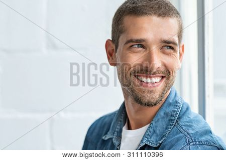 Confident young man looking away with big smile. Happy handsome guy looking through window thinking