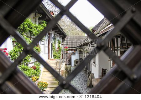 View of cozy old courtyard through rhombus window with cells in gate. Medieval narrow cobbled street and small ancient houses in Novy Svet, Hradcany district. Young greenery on white walls. Nobody stock photo