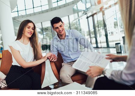 Financial advisor showing report to young couple for their investment. Salesman and positive couple talking about purchase. Happy couple consulting financial agent for loan. stock photo