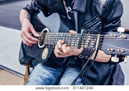 Close Up Of A Man In A Leather Jacket Playing An Old Black Acoustic Guitar