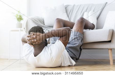 Home workout. Active african man doing abs training and crunches in living room, panorama stock photo