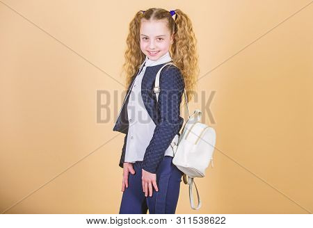 Stylish mini backpack. Learn how fit backpack correctly. Girl little fashionable cutie carry backpack. Popular useful fashion accessory. Schoolgirl with small leather backpack. Carry bag comfortable stock photo