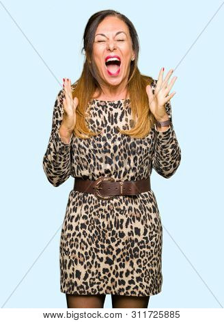 Beautiful middle age woman wearing leopard animal print dress celebrating mad and crazy for success with arms raised and closed eyes screaming excited. Winner concept stock photo