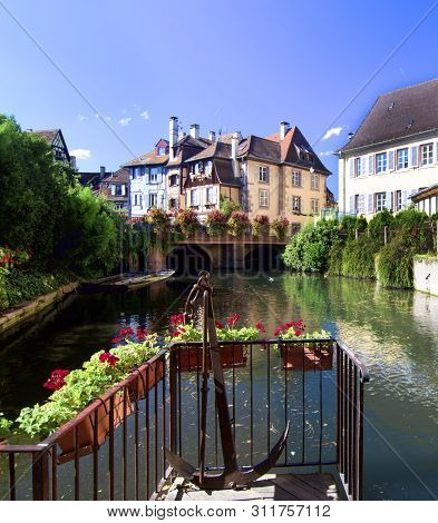 Colorful View from Channel to Historical Buildings and Beautiful Flower Pots on Blue Sky background Outdoors. Colmar, France stock photo