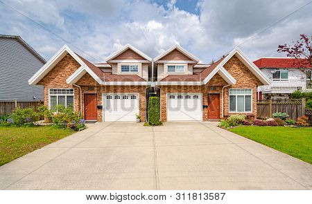 Residential duplex house with concrete drive way and green lawns in front. Two family dwelling with green lawn in front stock photo