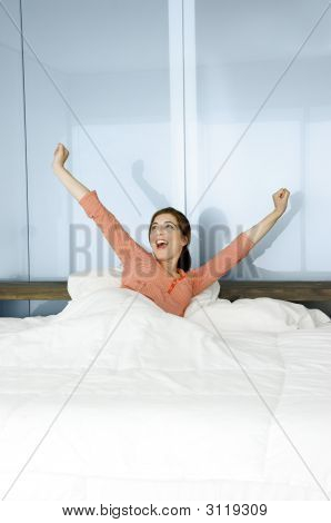 Portrait of a beautiful woman on a bed waking up. stock photo