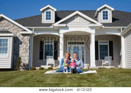 Happy Family in Front of Their Home stock photo