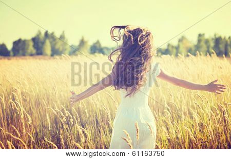 Beauty Girl Outdoors enjoying nature. Beautiful Teenage Model girl in white dress running on the Spr
