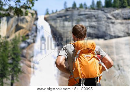 Hiker hiking with backpack looking at waterfall in Yosemite park in beautiful summer nature landscap