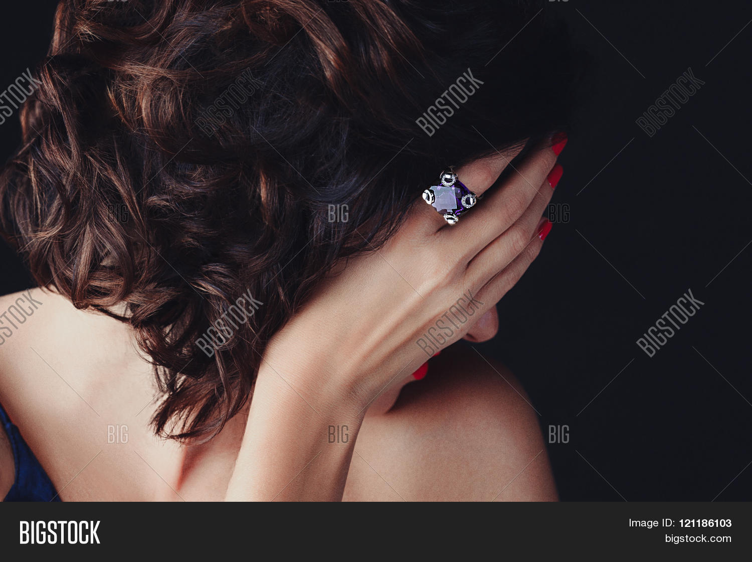 A luxurios stunning woman with gorgeous hair covering her face, her delicate hand with nails painted  red, and a large supphire ring on its index finger.