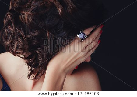 A luxurios stunning woman with gorgeous hair covering her face, her delicate hand with nails painted  red, and a large supphire ring on its index finger. stock photo