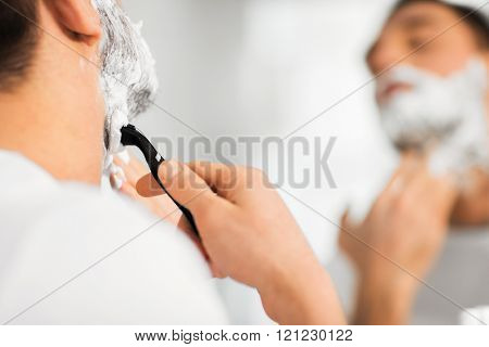 beauty, hygiene, shaving, grooming and people concept - close up of young man looking to mirror and shaving beard with manual razor blade at home bathroom stock photo