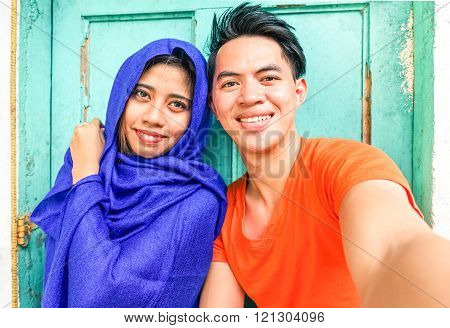 Young Asian Muslim Couple Taking Selfie Next To Old Green Wooden Door -