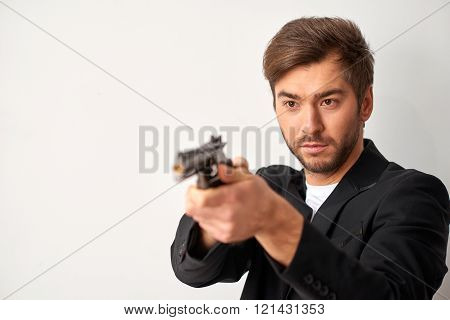Looking dangerous. Studio shot of attractive young man holding and pointing a gun isolated on white background. stock photo