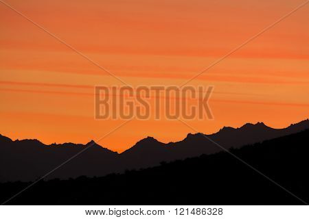 Dramatic sunset in the hills of Palm Springs shows beautiful striations in a deep orange sky stock photo