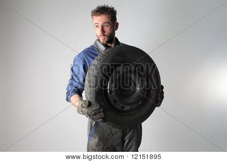 Portrait of auto mechanic holding a  wheel  isolated on a white background stock photo