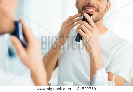 beauty, shaving, grooming and people concept - close up of young man looking to mirror and shaving beard with trimmer or electric shaver at home bathroom stock photo