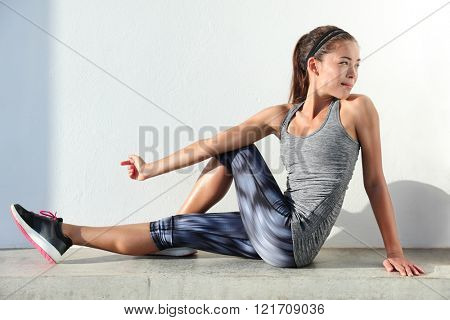Fitness woman stretching legs doing pilates leg stretches exercises in outdoor gym. Asian athlete ex