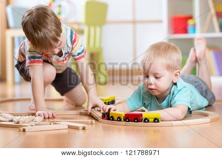 Cute children playing with wooden train. Toddler kids play with blocks and trains. Boys building toy