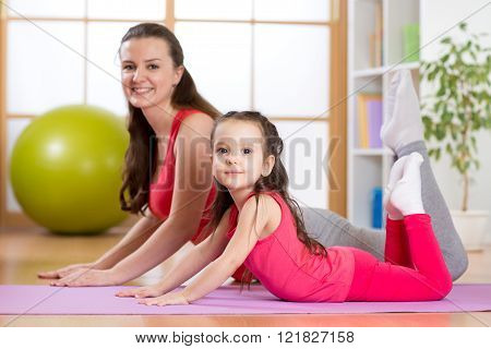 Mom and kid do gymnastics. Family sports
