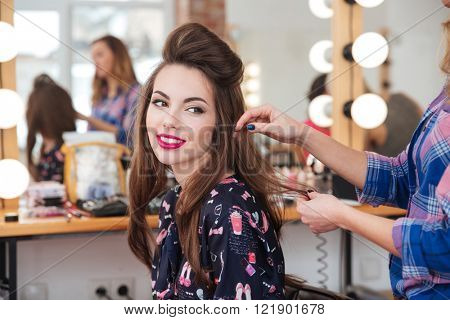 Female hairdresser standing and making hairstyle to cute lovely young woman in beauty salon stock photo