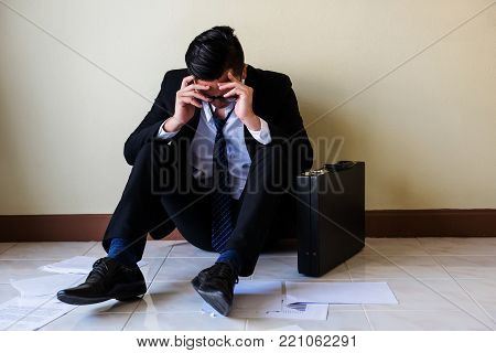 Close up of stressed young Asian businessman with glasses raise hands to touch his head and sit on floor. Feeling bad and headache against job after getting lay off or fired in office. stock photo