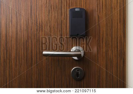 Hotel electronic card lock on wooden door. Security, room service, privacy concept stock photo