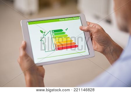 Hand holding digital tablet and looking at house efficiency rating. Detail of house efficiency ratin