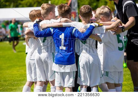 Young football soccer players in sportswear. Coach Motivating Kids In Sport. Youth sports team with football coach. Pep talk with coach before the final match. Soccer school tournament stock photo