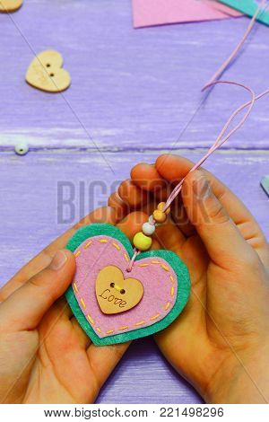 Small child holds a felt heart pendant necklace in his hands. Child made a felt heart pendant necklace. Kids gift for mother on Valentines day, Mothers day or birthday. Creative idea for kids activity stock photo