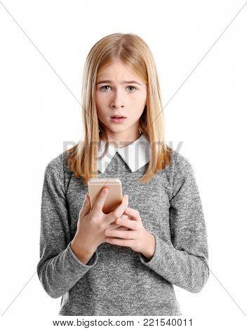 Sad teenage girl with smartphone on white background stock photo