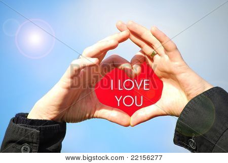 I love you - sign language heart made by hands against blue sky and sunlight stock photo