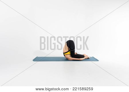 Sporty young woman doing yoga practice isolated on white background stock photo