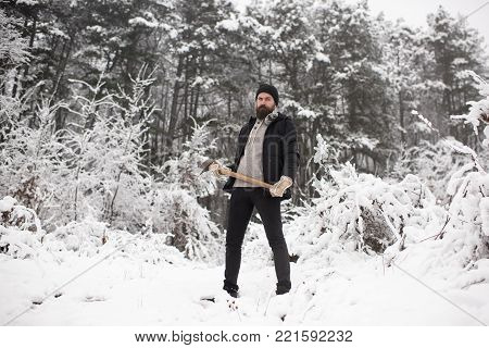 Man lumberjack in thermal jacket with ax. Camping, traveling and winter rest. Bearded man with axe in snowy forest. beard care in winter, beard warm in winter. Temperature, cold snap, snowfall. stock photo