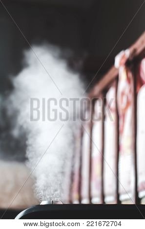 The steam from the humidifier night the bedroom, next to the crib stock photo