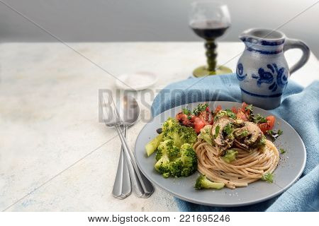 whole grain spaghetti with chamignons, broccoli and tomatoes, blue napkin on a rustic light table, wine jug and glas in the background, copy space, selected focus, narrow depth of field stock photo