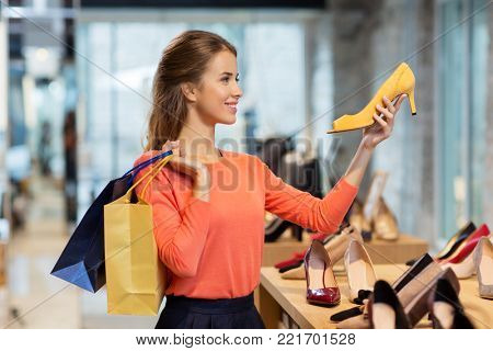 sale, fashion and people concept - happy young woman with shopping bags choosing shoes at store stock photo