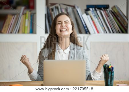 Excited female student feels euphoric celebrating online win success achievement result, young woman happy about good email news, motivated by great offer or new opportunity, passed exam, got a job