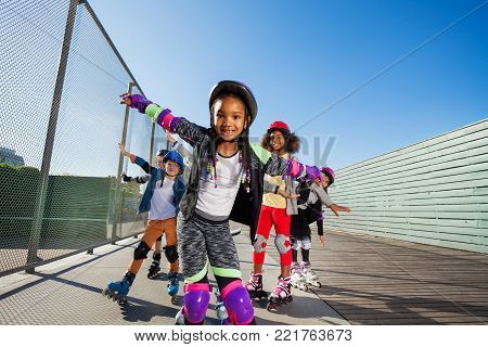 African young girl rollerblading with her friends in helmet, protective gear and rollerblades outdoors stock photo