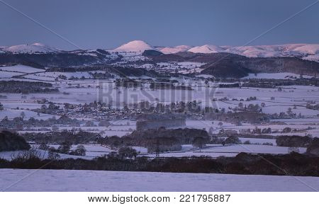 Shropshire Hills covered in in snow and morning mists over winter land at dawn stock photo