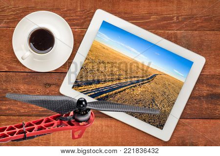 dirt ranch road  in Pawnee National Grassland in northern Colorado, fall or winter scenery, reviewing an aerial image on a digital tbalet with a cup of coffee and drone propeller stock photo