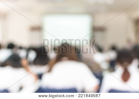 School classroom blurred background of college or university students back view sitting in class in seating rows studying learning course in lecture room with white projector screen in front stock photo