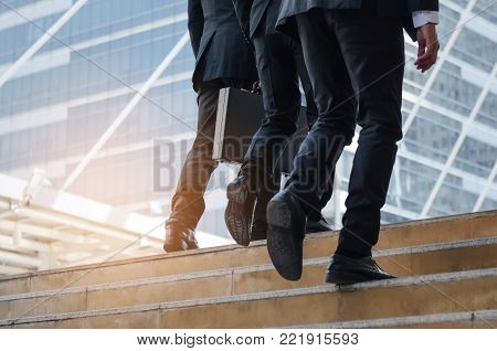group of young handsome business man holding briefcase and walking up stairs going to work time at morning in the city, determination, confidence, lifestyle, rush hour, grow up and successful concept stock photo
