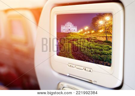 Aircraft In flight entertainment seat-back TV screens showing a picture of a Famous Macau`s landmark, Ruins of St. Paul`s at night stock photo