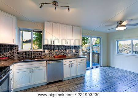 L-shape kitchen room design with white cabinets, brown granite countertops, mosaic backsplash, built in stainless steel appliances and wide plank hardwood floor. stock photo